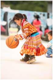 小女孩认真的拍打着篮球